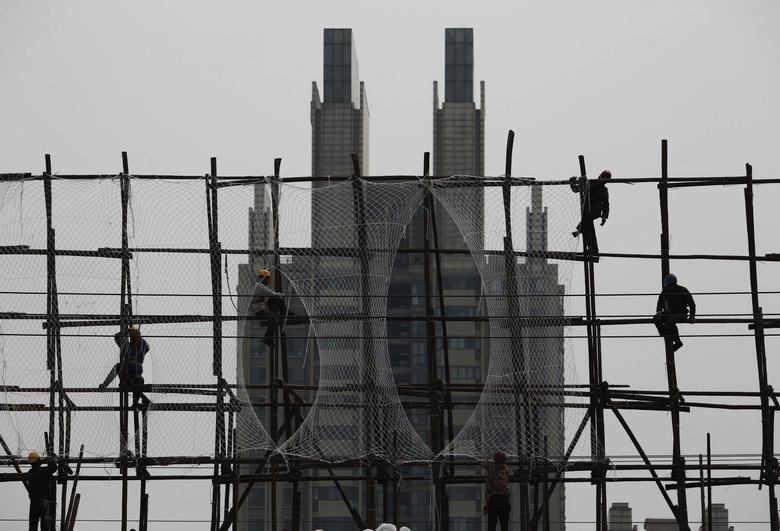 Labourers work on the scaffolding of a construction site for a new residential building in Beijing, May 6, 2014. REUTERS/Kim Kyung-Hoon