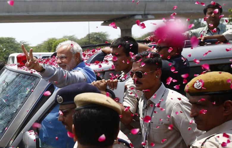 Hindu nationalist Narendra Modi (L), the prime ministerial candidate for India's Bharatiya Janata Party (BJP), gestures to his supporters during a road show in New Delhi May 17, 2014. REUTERS/Anindito Mukherjee