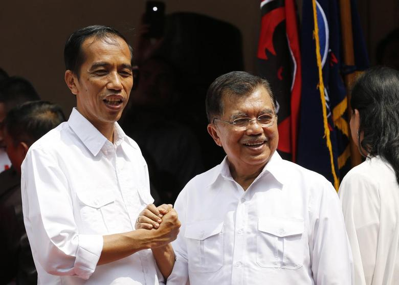 Indonesian presidential candidate Joko ''Jokowi'' Widodo (L) and his vice presidential running mate Jusuf Kalla shake hands during an event declaring their bid in the upcoming July 9 election, in Jakarta May 19, 2014. REUTERS/Stringer