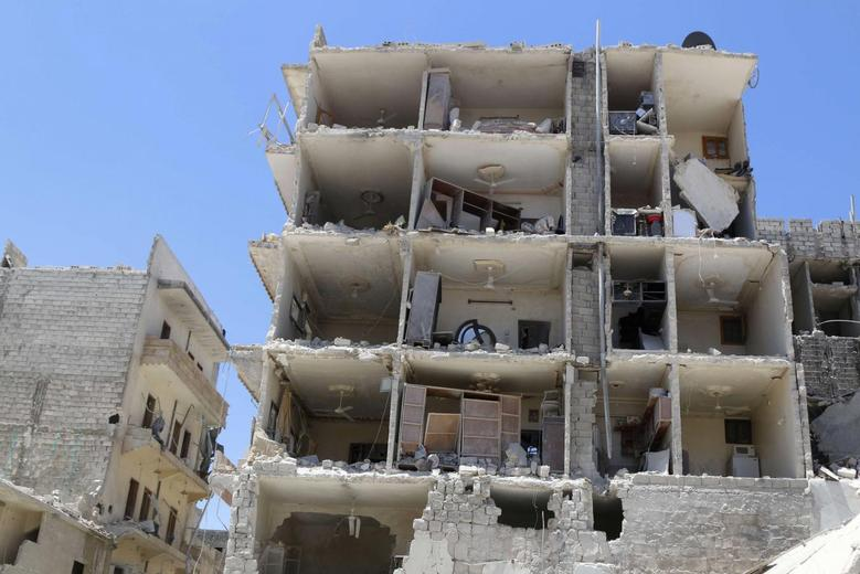 A damaged building is pictured at a site hit by what activists said were two barrel bombs dropped by forces loyal to Syria's President Bashar al-Assad in al-Katerji district in Aleppo May 18, 2014. REUTERS/Hosam Katan