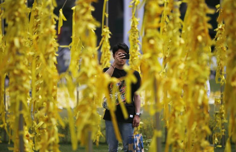 A man takes photographs of a ''Yellow Ribbon Garden'', dedicated to dead and missing passenger of sunken ferry Sewol, at Seoul City Hall Plaza in Seoul May 19, 2014.REUTERS/Kim Hong-Ji