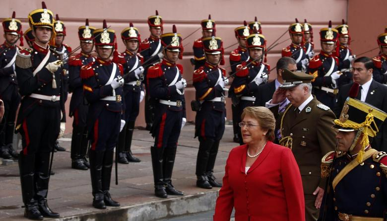 Chile's President Michelle Bachelet walks past honour guards as she arrives at the Casa Rosada Presidential Palace for a meeting with Argentina's President Cristina Fernandez de Kirchner in Buenos Aires May 12, 2014. REUTERS/Marcos Brindicci