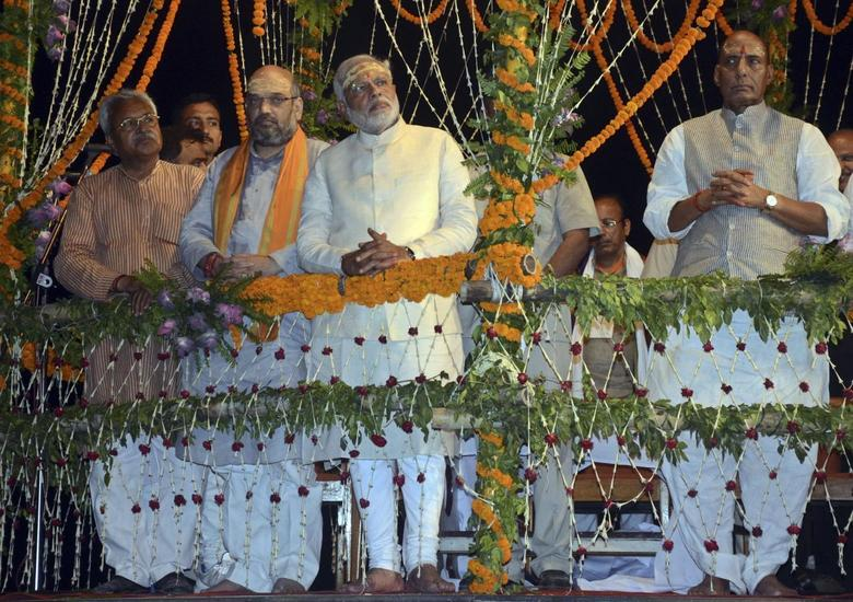 Hindu nationalist Narendra Modi (C), India's prime minister-elect from the Bharatiya Janata Party (BJP), watches a ritual known as ''Aarti'' during evening prayers on the banks of river Ganges at Varanasi, in the northern Indian state of Uttar Pradesh, May 17, 2014. REUTERS/Pawan Kumar