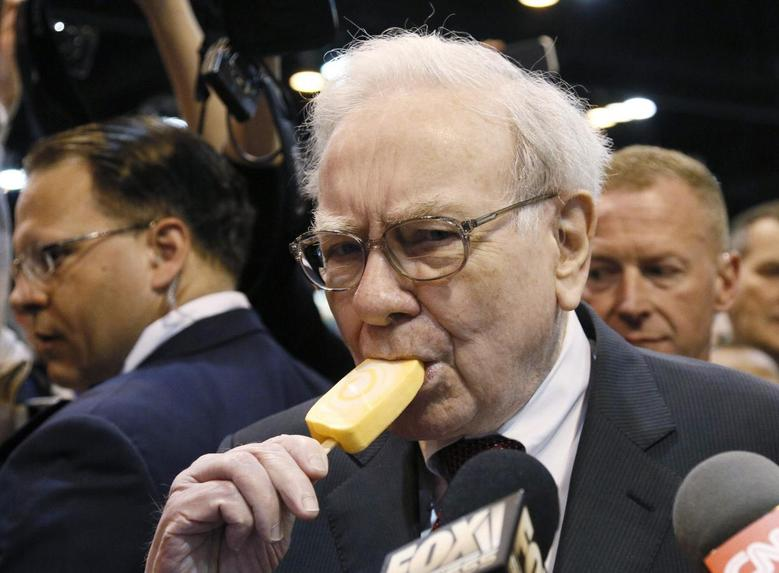 Berkshire Hathaway CEO Warren Buffett bites into an ice cream during a trade show at the company's annual meeting in Omaha, Nebraska May 3, 2014. REUTERS/Rick Wilking