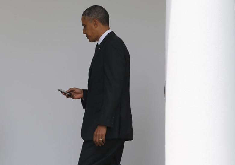 President Barack Obama checks his Blackberry smartphone upon his return from a trip to New York to attend the opening of the National September 11 Memorial Museum in New York, as he walks into the West Wing of the White House in Washington, May 15, 2014. REUTERS/Jim Bourg