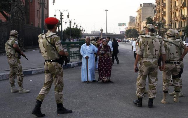 Pedestrians look as the Egyptian army soldiers divert traffic away from the front of the Egyptian museum in Cairo, July 9, 2013. REUTERS/Asmaa Waguih