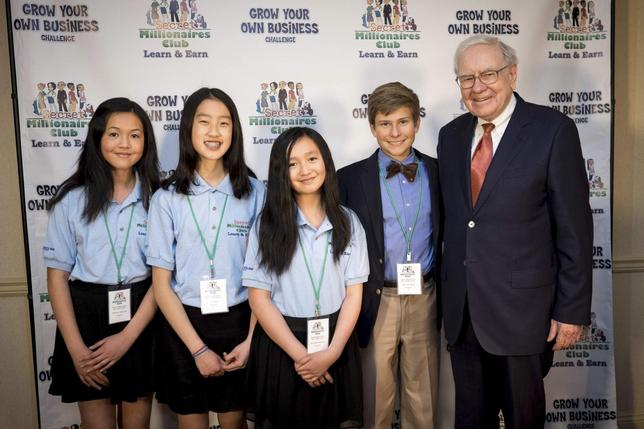 Krystal Graylin, Kei Chua Allyson Graylin (the group winners) and Jake Johnson (the individual winner) stand with Warren Buffett at the Marriott Hotel in Omaha, Nebraska, in this undated handout photo courtesy of Eric Francis photography. REUTERS/Eric Francis photography/Handout via Reuters