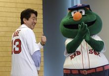 Japan's Prime Minister Shinzo Abe (L) smiles as he wears a jersey of the Boston Red Sox, while Red Sox mascot Wally (R) looks on at Abe's office in Tokyo January 21, 2014. REUTERS/Yoshikazu Tsuno/Pool