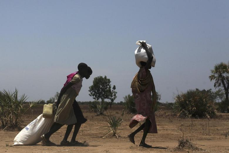 Women carry food at a food distribution site in Nyal, Unity State, April 1, 2014. REUTERS/Andreea Campeanu