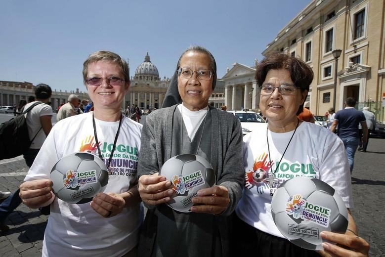 Nuns Gabriella Bottani (L), Estrella Castalone (C) and Carmen Sammut hold the logo of an international campaign called ''Play in Favour of Life-Denounce Human Trafficking,'' on the risks they say will be associated with the June-July games, as they pose in front of Saint Peter's basilica in Rome May 20 2014. REUTERS/Tony Gentile