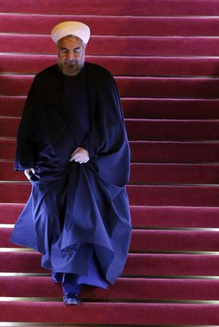 Iran's President Hassan Rouhani walks down a stairs as he arrives at Pudong International Airport, ahead of the fourth Conference on Interaction and Confidence Building Measures in Asia (CICA) summit in Shanghai May 20, 2014. REUTERS/Carlos Barria