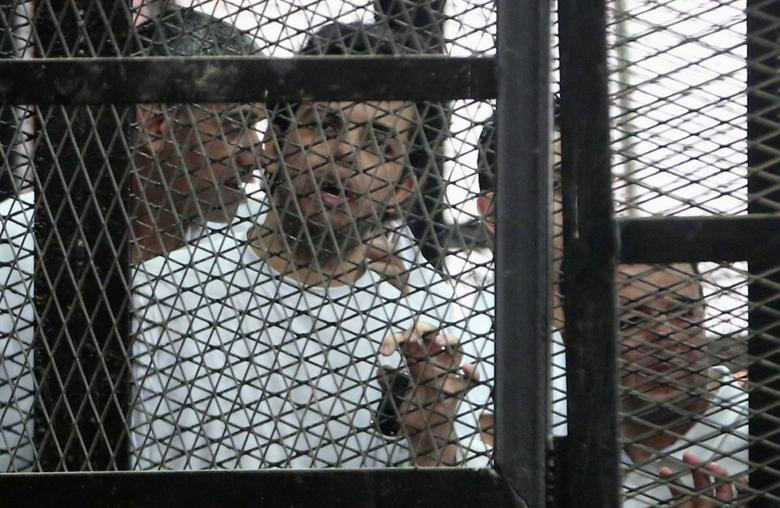 Al Jazeera's hunger striking journalist Abdullah Elshamy stands behind bars with other prisoners at a court in Cairo May 15, 2014. REUTERS/Stringer
