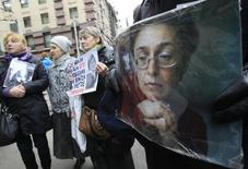 People hold portraits of slain journalist Anna Politkovskaya on the sixth anniversary of her death, next to her block of flats in central Moscow October 7, 2012. REUTERS/Sergei Karpukhin