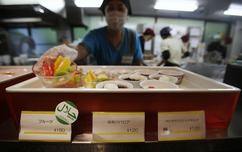 A staff shows a bowl of cut fruit, above a ''halal certified'' sign, at a dining hall in the Kanda University of International Studies in Chiba, east of Tokyo May 13, 2014. REUTERS/Yuya Shino