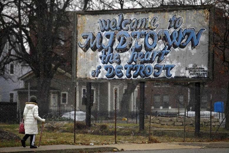 A woman walks through the Midtown neighborhood of Detroit, Michigan December 3, 2013. REUTERS/Joshua Lott