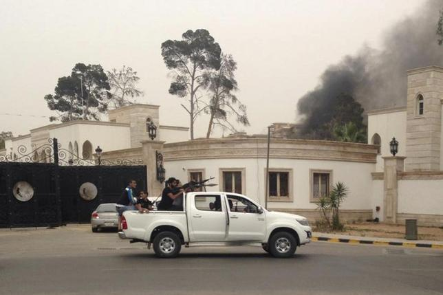 Armed men aim their weapons from a vehicle as smoke rises in the background near the General National Congress in Tripoli May 18, 2014. REUTERS/Stringer