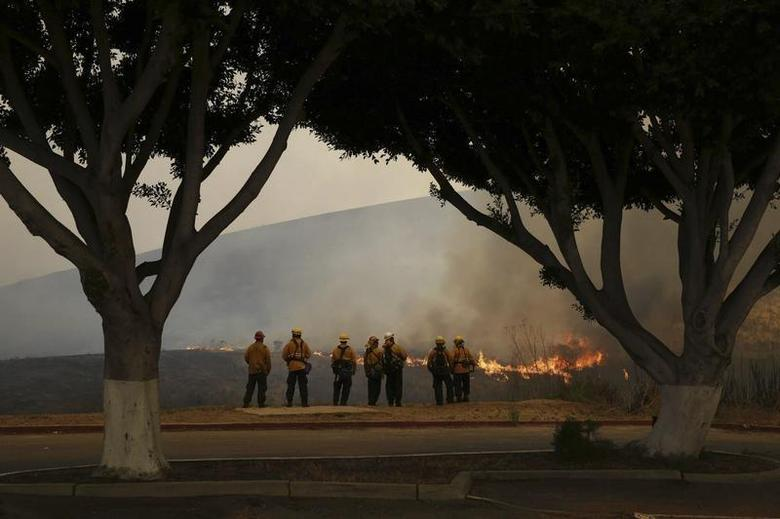 Firefighters watch the Las Pulgas Fire at Camp Pendleton, California in this May 16, 2014 handout photo from the USMC. REUTERS/Cpl. Sarah Wolff/USMC/Handout via Reuters