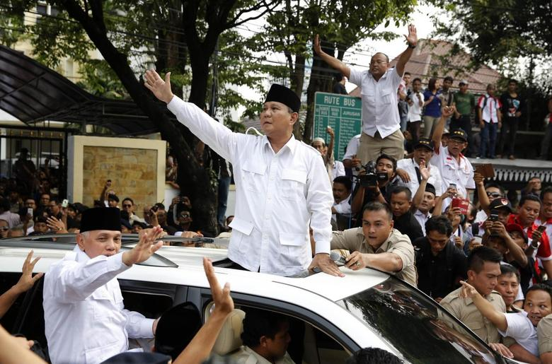 Indonesian presidential candidate Prabowo Subianto (C) and his vice presidential running mate Hatta Rajasa wave to supporters after registering at the Election Commission for the upcoming July 9 election in Jakarta May 20, 2014. REUTERS/Stringer