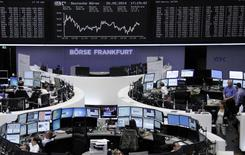Traders are pictured at their desks in front of the DAX board at the Frankfurt stock exchange May 20, 2014. REUTERS/Remote/Stringer