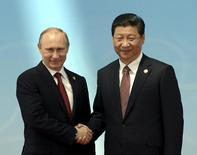 Russia's President Vladimir Putin (L) is greeted by his Chinese counterpart Xi Jinping before the opening ceremony of the fourth Conference on Interaction and Confidence Building Measures in Asia (CICA) summit in Shanghai May 21, 2014. REUTERS/Mark Ralston/Pool