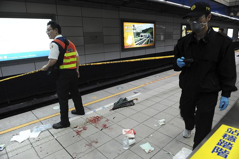 A crime scene investigator walks at the scene of a knife attack at a subway platform in the Taipei Metro Jiangzicui station in New Taipei city May 21, 2014. REUTERS/Stringer