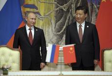 Le président russe, Vladimir Poutine (à gauche), et son homologue chinois, Xi Jinping, assistent à la cérémonie de signature d'un accord sur la fourniture de gaz russe à la Chine. Fruit de plus de dix ans de négociations, l'accord prévoit l'exportation vers la Chine de 38 milliards de mètres cubes de gaz russe par an pendant trois décennies, pour un montant total estimé à plus de 400 milliards de dollars (293 milliards d'euros).. /Photo prise le 21 mai 2014/REUTERS/Alexei Druzhinin/RIA Novosti/Kremlin