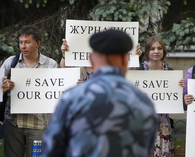Russian journalists hold placards and shout slogans during a protest outside the Ukrainian embassy in Moscow May 21, 2014. REUTERS/Sergei Karpukhin