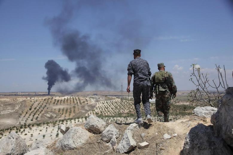 Syrian army soldiers loyal to President Bashar al-Assad walk on Hilan Hill, as smoke rises in the background from a village they claim to be shelling, May 21, 2014. REUTERS/George Ourfalian