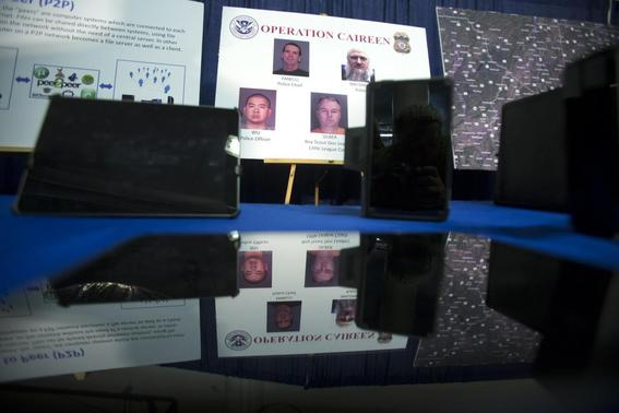 Photos of people arrested in a sting operation are reflected in a seized tablet computer following a news conference to announce the arrest of 71 individuals for sharing child pornography online in New York May 21, 2014. REUTERS-Carlo Allegri