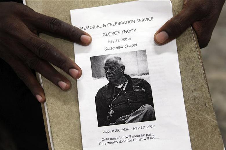 A person holds a flyer announcing a memorial service for U.S. missionary George Knoop, an elder with the Quisqueya Chapel, during the service in Port-au-Prince, May 21, 2014. REUTERS/Marie Arago
