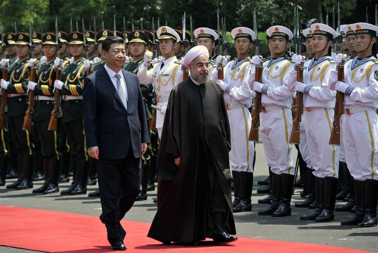 Iranian President Hassan Rouhani (R) and Chinese President Xi Jinping review an honour guard during the welcome ceremony at the Xijiao State Guesthouse in Shanghai, May 22, 2014. REUTERS/Kyodo/Kenzaburo Fukuhara