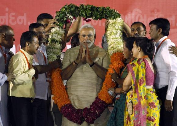 Hindu nationalist Narendra Modi, who will be the next prime minister of India, wears a garland presented to him by his supporters at a public meeting in Ahmedabad May 20, 2014. REUTERS/Amit Dave