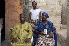 Chiroma Maina (R) holds a picture of her abducted daughter Comfort Amos, next to her husband Jonah and her daughter Helen, at their home in Maiduguri May 21, 2014. REUTERS/Joe Penney
