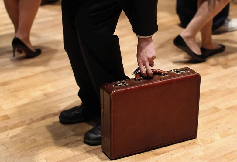 A man grabs his briefcase as he waits in line to speak with employers at the UJA-Federation Connect to Care job fair in New York, March 21, 2012. REUTERS/Shannon Stapleton