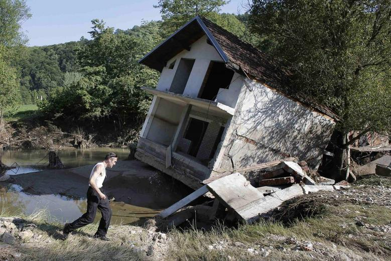 A man walks past a house tilted by floods in the town of Valjevo, southwest from Belgrade May 21, 2014. REUTERS/Marko Djurica