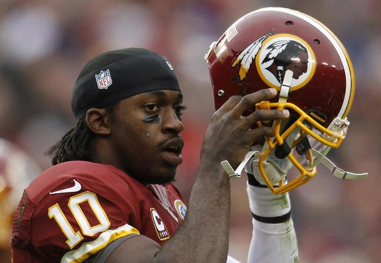 Washington Redskins quarterback Robert Griffin III puts his helmet back on after being tackled by the Baltimore Ravens defense in the first half of their NFL football game in Landover, Maryland in this December 9, 2012 file photo. REUTERS/Gary Cameron/Files
