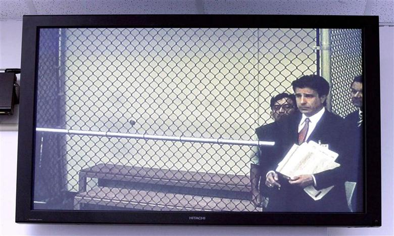 Isidro Garcia, 41, (rear C) appears behind his attorney Charles Frisco in a jailhouse video court hearing screened on a monitor in Santa Ana, California, May 22, 2014. REUTERS/Alex Gallardo