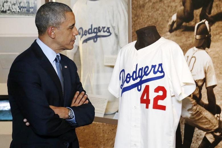 U.S. President Barack Obama looks at a Jackie Robinson jersey as he tours the National Baseball Hall of Fame in Cooperstown, New York, May 22, 2014. REUTERS/Jonathan Ernst