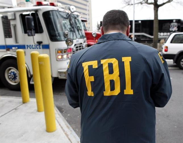 An FBI special agent investigates a scene in Queens, New York March 25, 2010. REUTERS/Chip East''