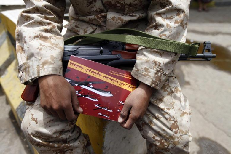 A soldier carries an anti-U.S. drone booklet as people chant slogans against U.S. drone strikes outside the Yemeni House of Representatives in Sanaa April 24, 2014. REUTERS/Mohamed al-Sayaghi