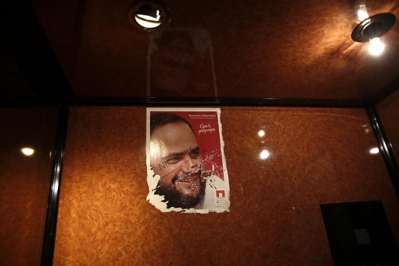 A poster featuring a portrait of candidate for councillor Evangelos Marinakis is seen inside an elevator in Piraeus port town, near Athens May 22, 2014. BREUTERS/Yorgos Karahalis