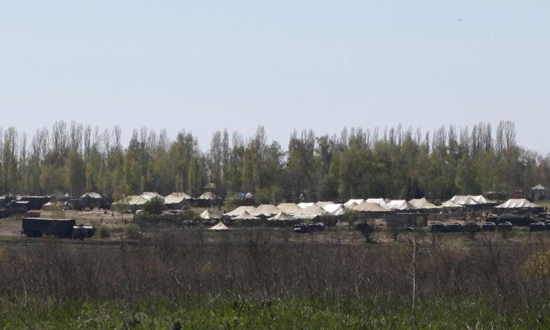 Russian military vehicles and army tents are seen in a field outside the village of Severny in Belgorod region near the Russian-Ukrainian border, April 25, 2014. REUTERS/Sergei Khakhalev