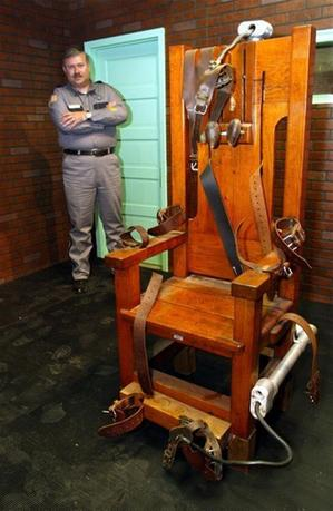 Aaron Dickson, President of the Board of Directors of the Texas Prison Museum stands on November 19, 2002 with ''Old Sparky,'' the Texas electric chair in which 361 killers were executed. - RTXLMWL