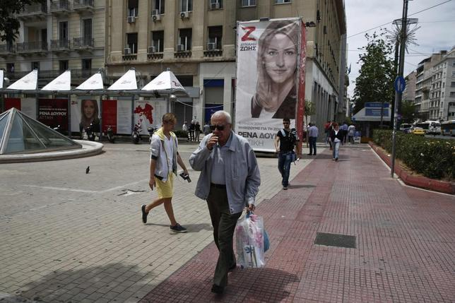 People walk past a pre-election kiosk of candidate Rena Dourou in Athens May 13, 2014. REUTERS/Yorgos Karahalis