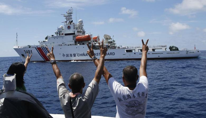 Philippine Marines and a local television reporter (L) gesture towards a Chinese Coast Guard vessel, which twice attempted to block a Philippine government supply ship from reaching the disputed Second Thomas Shoal, part of the Spratly Islands, in the South China Sea March 29, 2014. REUTERS/Erik De Castro