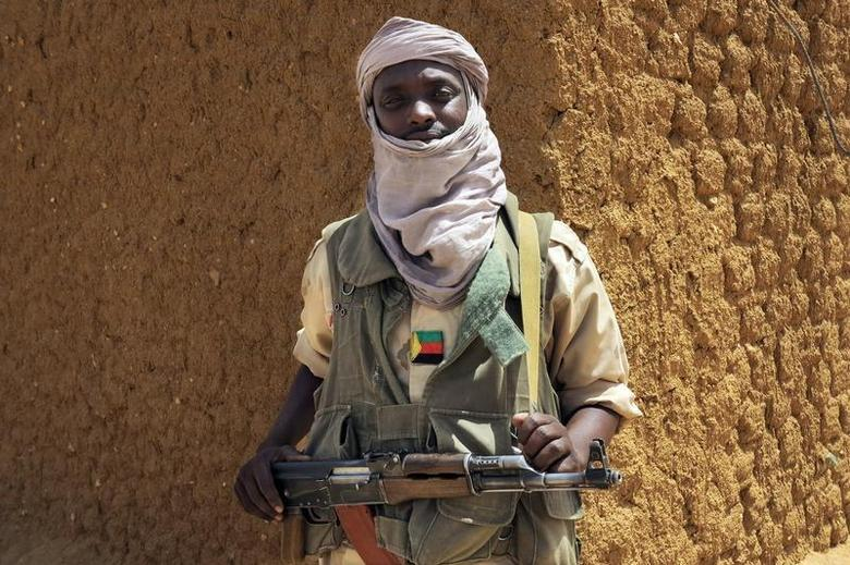 A fighter with the Tuareg separatist group MNLA (National Movement for the Liberation of Azawad) stands guard outside the local regional assembly in Kidal June 23, 2013. REUTERS/Adama Diarra