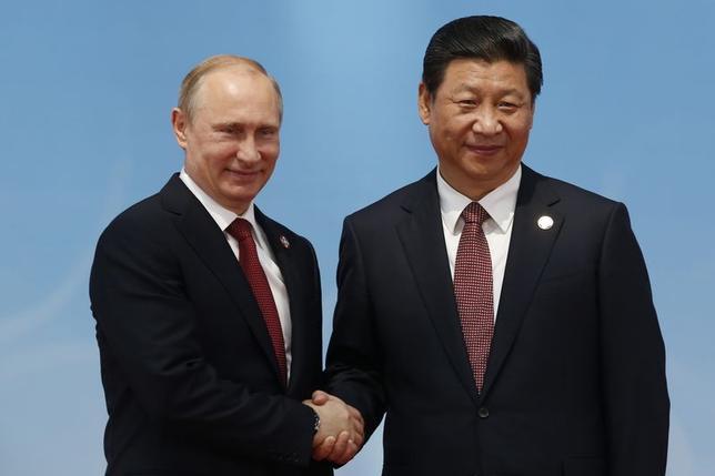 5月22日、ロシアのプーチン大統領(左)はクリミア編入によって政治的な支持を長年にわたって確保する見通しだが、中国とのガス供給契約はそれを上回る朗報だ。写真右は中国の習国家主席。上海で21日撮影(2014年 ロイター/Aly Song)