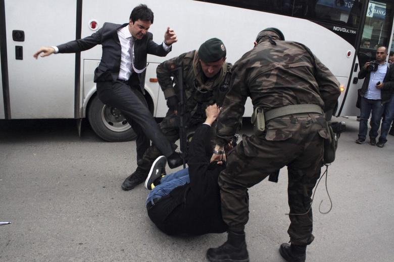A protester is kicked by Yusuf Yerkel (L), advisor to Turkey's Prime Minister Tayyip Erdogan, as Special Forces police officers detain him during a protest against Erdogan's visit to Soma, a district in Turkey's western province of Manisa May 14, 2014. REUTERS/Mehmet Emin Al/Depo Photos