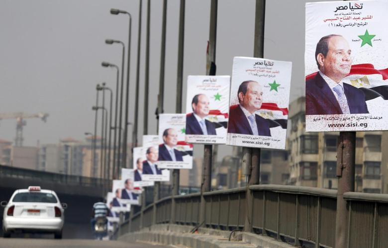 A car travels past posters of presidential candidate and Egypt's former army chief and Abdel Fattah al-Sisi on a bridge in Cairo May 22, 2014. REUTERS/Amr Abdallah Dalsh