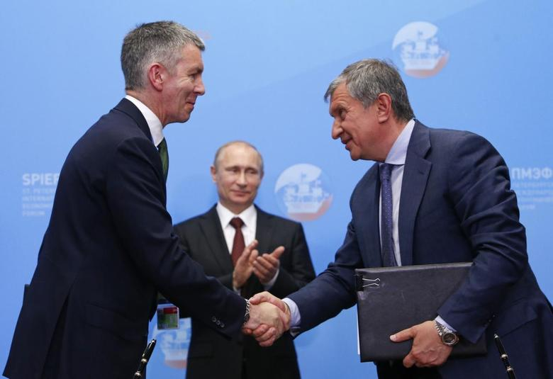 Rosneft President Igor Sechin (R) shakes hands with BP Russia head David Campbell as Russia's President Vladimir Putin looks on during a signing ceremony at the St. Petersburg International Economic Forum 2014 (SPIEF 2014) in St. Petersburg May 24, 2014. REUTERS/Sergei Karpukhin